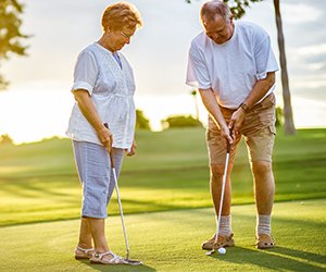 Picture of mature couple playing golf on beautiful day