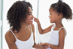 mother and daughter with pretty skin applying lotion to face