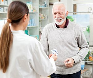 Picture of pharmacists talking with male customer about medications
