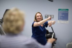 Nurse helps during cardiac rehab class.