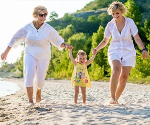 Picture of three generations of females playing along the beach