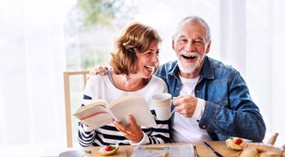 Older couple laughing enjoying a cup of coffee