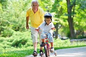 older male teaching young boy to ride bike