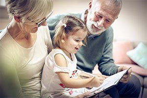 picture of grandparents helping grandchild learn to write