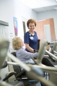 Nurse watches patient on exercise equipment during cardiac rehab.