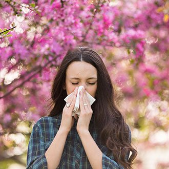 Person with allergies blows nose.