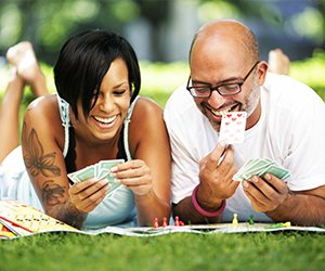 Picture of couple outside playing cards and thinking about next move in game